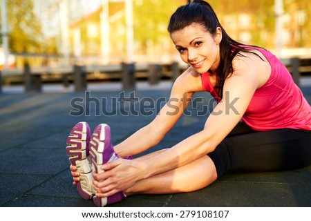 Woman stretching hamstrings on floor, hands on feet and smiling at camera. - stock photo