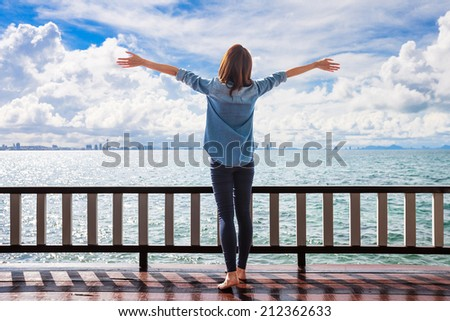 Woman stretching her arms to enjoy the fresh air of the sea at the balcony under cloudy sky - stock photo