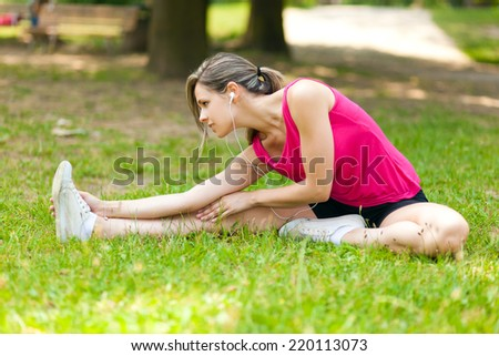 Woman stretching her leg while sitting on the grass  - stock photo