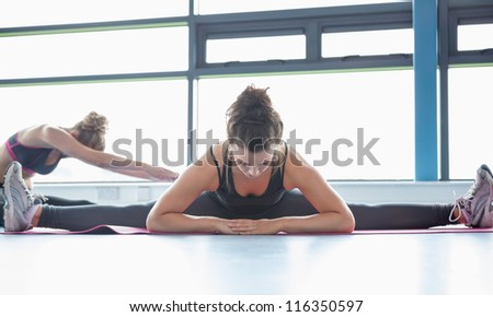Woman stretching her legs in a gym - stock photo