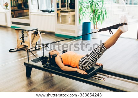 Woman stretching in a pilates reformer, close-up - stock photo