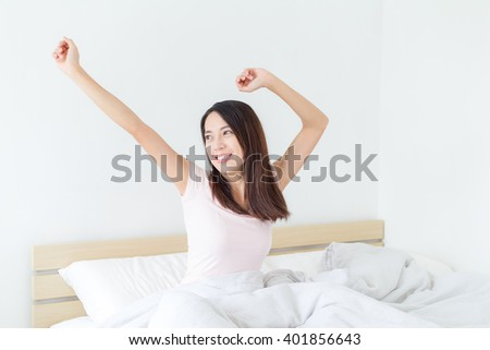 Woman stretching in bed after wake up - stock photo