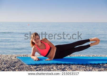 Woman stretching in yoga exercise fitness training at coastline at sunset - stock photo