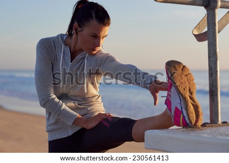 woman stretching leg muscle before early morning run workout on beach - stock photo