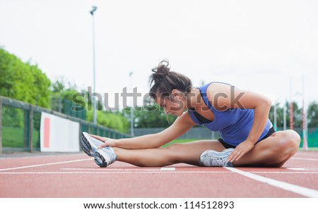 Woman stretching on a track in a stadium - stock photo