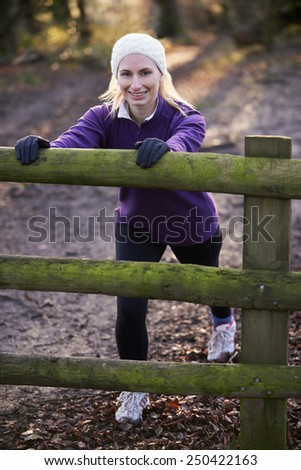Woman Stretching On Run Through Winter Woodland - stock photo