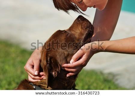 Woman stroking dog - stock photo
