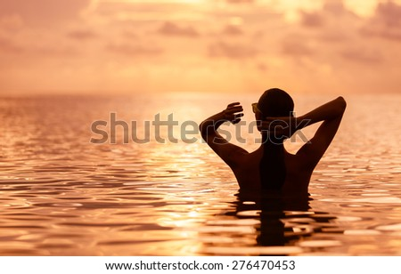 Woman stroking her hair back in a beautiful setting. - stock photo