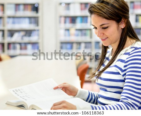 Woman studying at the library and reading a book - stock photo