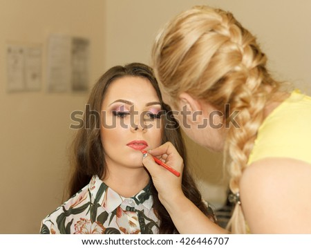 Woman stylist does a make-up to the beautiful girl - stock photo