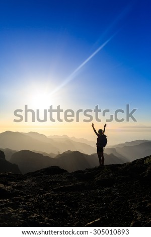 Woman successful climbing silhouette in mountains, accomplish motivation and inspiration in beautiful sunset and ocean. Hiker with arms up outstretched on mountain top, sunset inspirational landscape. - stock photo