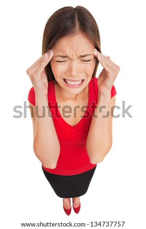 Woman suffering from a migraine headache rubbing her temples with her fingers and grimacing in pain, high angle full length studio portrait isolated on white background. Asian Caucasian female model. - stock photo