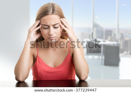 Woman suffering from an headache, holding her hand to the head, in an office - stock photo