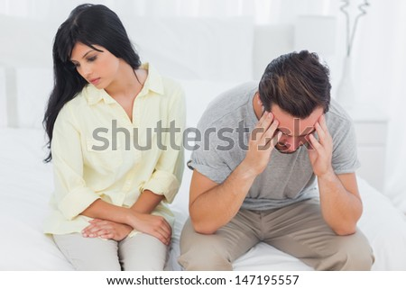 Woman sulking with boyfriend looking down during a fight at home in bedroom - stock photo