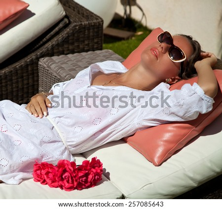 Woman sunbathing at tropical travel resort. Beautiful young woman lying on sun lounger near pool. Full relax and happiness - stock photo