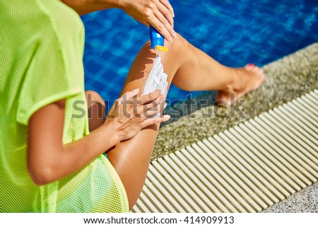 Woman sunbathing in bikini and applying sunscreen - stock photo
