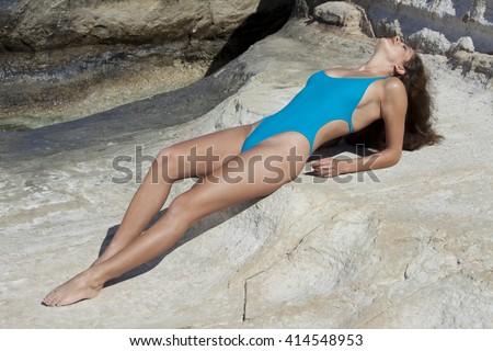 Woman sunbathing on the rocks wearing tight fitting and modish swimsuit. - stock photo
