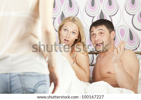Woman surprised her boyfriend cheating with another girl in bed - stock photo