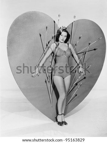 Woman surrounded by arrows on huge heart - stock photo
