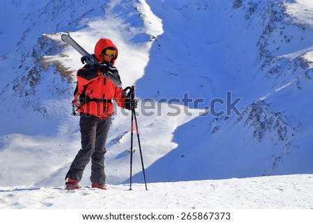 Woman surrounded by snowy mountains transports a pair of skies on the back  - stock photo