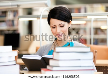 Woman surrounded with piles of books reads sitting at the desk at the library. Training process - stock photo