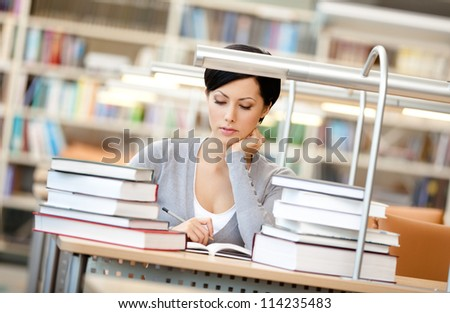 Woman surrounded with piles of books reads sitting at the desk at the reading hall. Information concept - stock photo