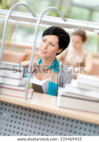 Woman surrounded with piles of books reads sitting at the table at the reading hall. Process of education - stock photo
