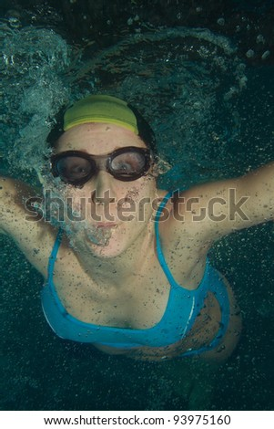 Woman swimmer underwater shoot in glasses and cap - stock photo
