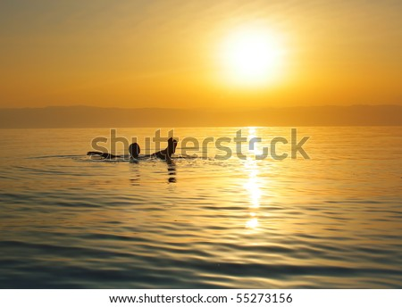 Woman swimming in salty water of a Dead Sea - stock photo