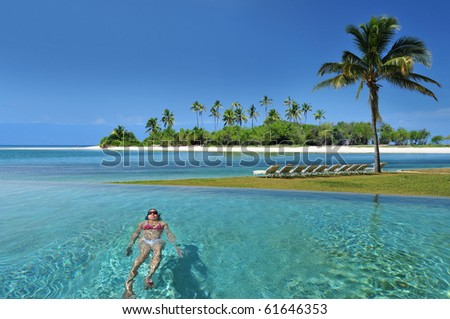 Woman swimming in the infinity pool under the sun in beautiful tropical beach resort in the Bahamas . - stock photo