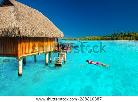 Woman swimming in tropical lagoon next to overwater villa - stock photo