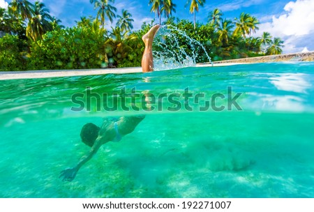 Woman swimming underwater, diving in turquoise transparent sea, wonderful tropical nature, summer adventure and tourism concept - stock photo