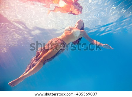 Woman swimming underwater in a blue pool - stock photo