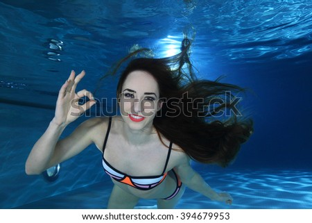 Woman swimming underwater in the pool - stock photo