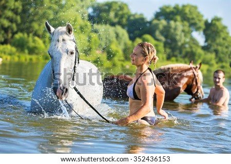 Woman swimming with a horse - stock photo