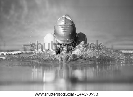 woman swims using the breaststroke in indoor pool - stock photo