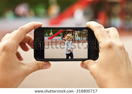 Woman taking a photo of baby girl with smartphone - POV shot - stock photo
