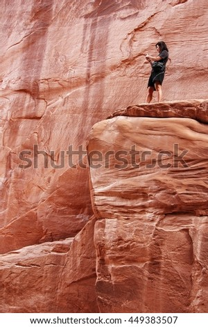 Woman taking a picture with her cell phone while climbing rocks - stock photo