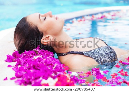 woman taking a spa bath in a pool full of petals - stock photo