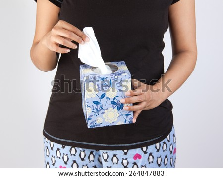 woman taking a tissue, wet wipe to clean - stock photo