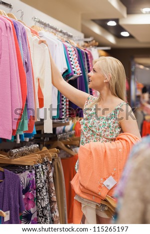 Woman taking clothes off the clothes rack - stock photo