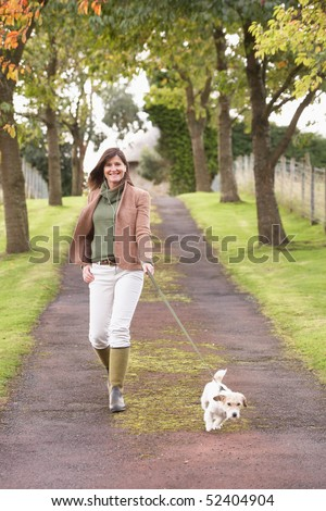 Woman Taking Dog For Walk Outdoors In Autumn Park - stock photo