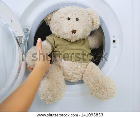 woman taking fluffy toy from washing machine - stock photo
