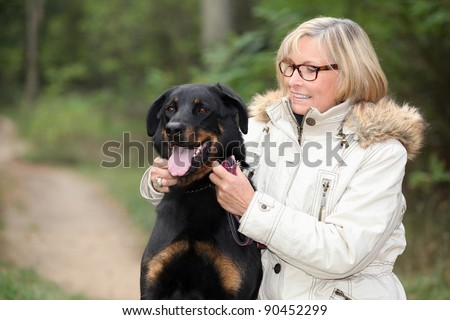 Woman taking her dog out for a walk - stock photo
