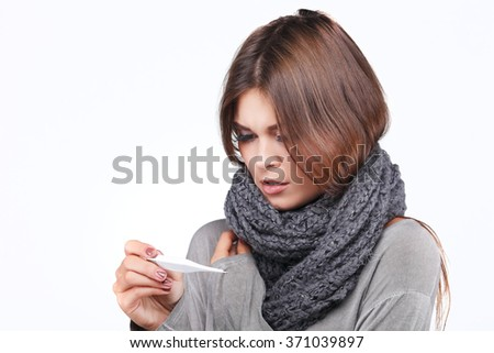 woman taking her temperature wile feeling sick and with fever, isolated on a white background - stock photo
