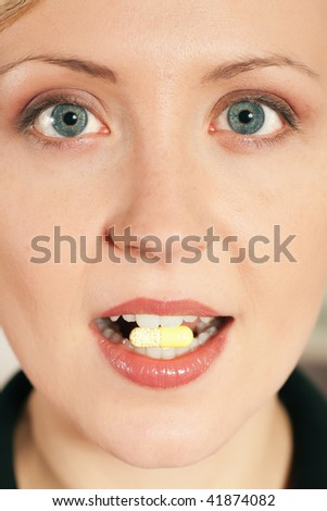 Woman taking in a pill - stock photo