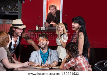 Woman taking orders for friend at mobile pizza restaurant - stock photo