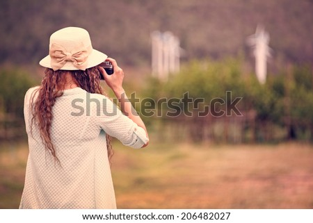 Woman taking photo in vintage style processing - stock photo
