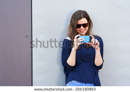 Woman taking photo with cellphone by the wall. Happy girl in city taking picture.