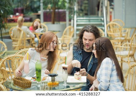 Woman taking picture of her friends in the coffee shop - stock photo
